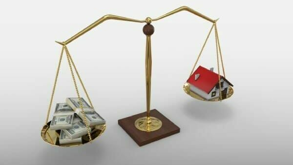 Money and a small house balancing on a scale, representing average mortgage payments in your state